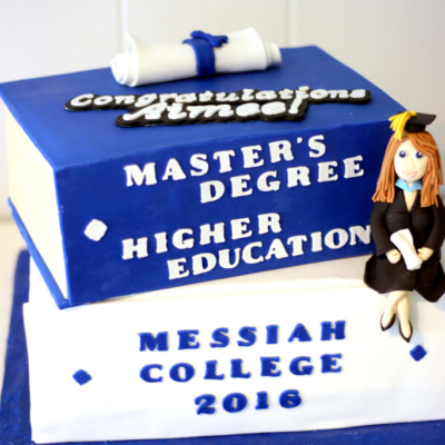 graduation cake with graduate sitting on textbooks