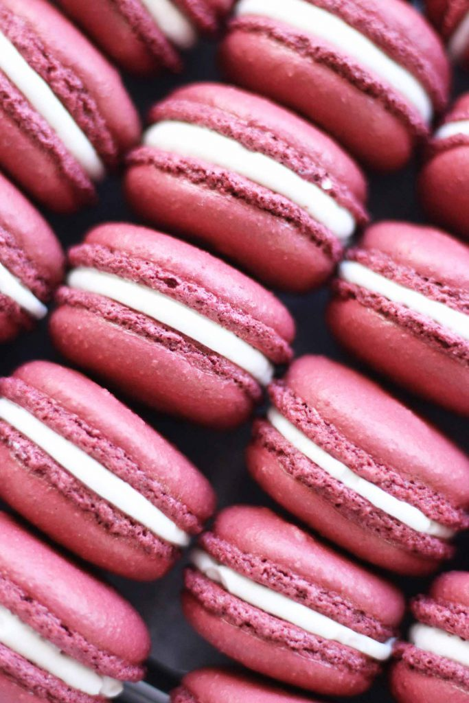 cranberry macarons with a dark pink cookie and white filling